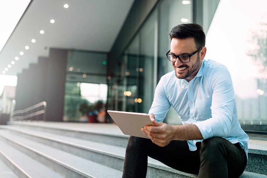 Client Center - Happy and Confident Businessman Using a Tablet to Easily Access His Insurance Account Information While Sitting Outside on the Steps of an Office Building