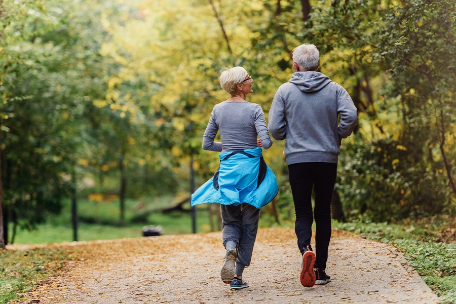 Employee Benefits - Cheerful Senior Couple Jogging in the Park