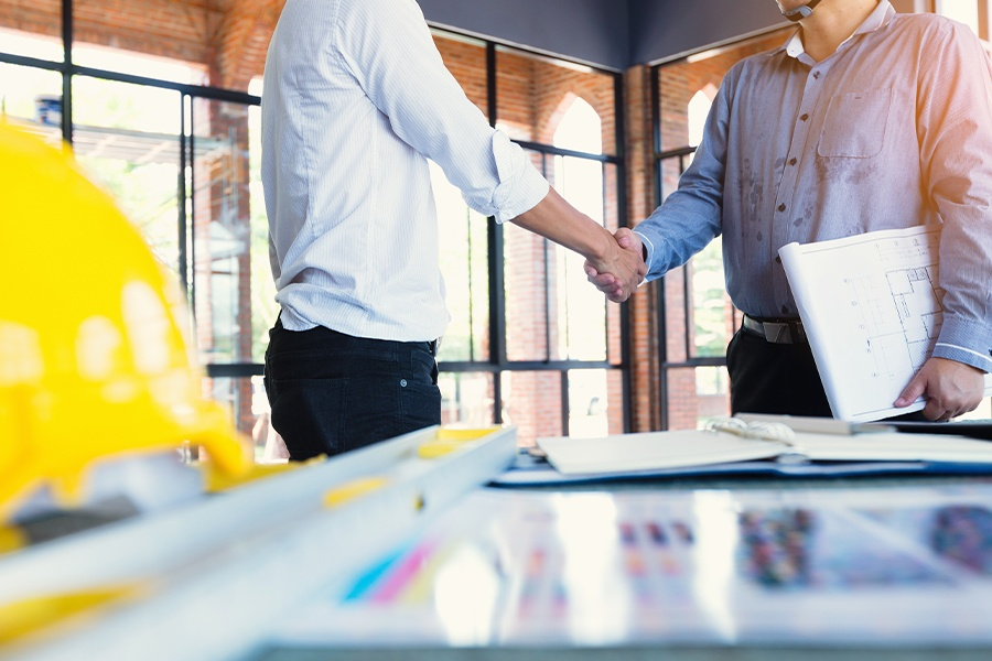 Specialized Business Insurance - Two Construction Engineers Shake Hands at Construction Site